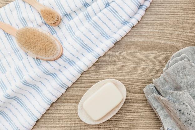 Erhöhte ansicht der bürste; handtuch; seife und schwamm auf holzuntergrund Kostenlose Fotos