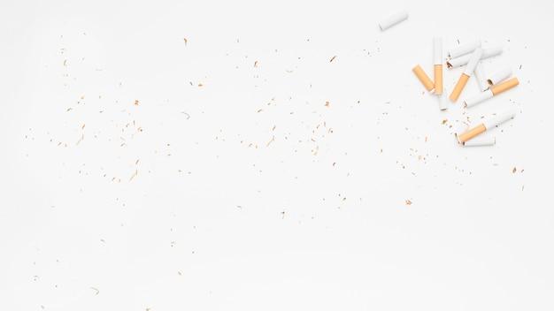 Erhöhte ansicht der defekten zigarette und des tabaks über weißer oberfläche Kostenlose Fotos