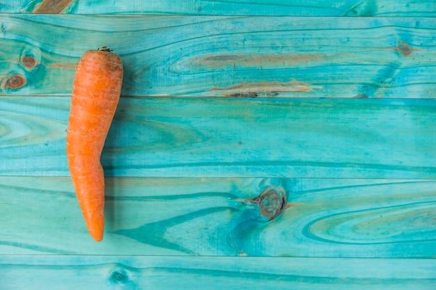 Erhöhte ansicht der frischen karotte auf türkis färbte hölzernen hintergrund Kostenlose Fotos