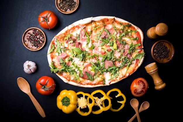 Erhöhte ansicht der frischen leckeren pizza mit gemüse umgeben; gewürze; und kräuter über küchentheke Kostenlose Fotos