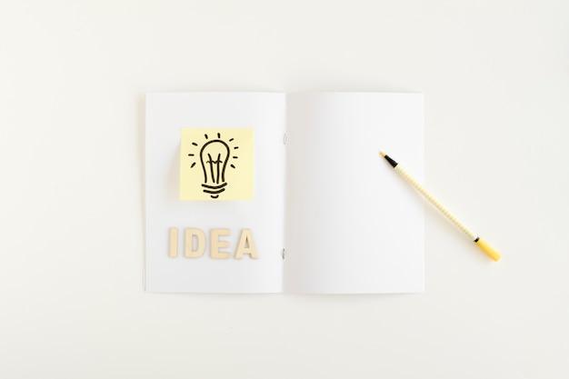 Erhöhte ansicht der glühlampe mit ideentext auf karte Kostenlose Fotos