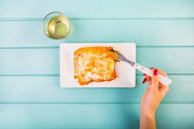 Erhöhte ansicht der hand der frau lasagne auf platte essend Kostenlose Fotos