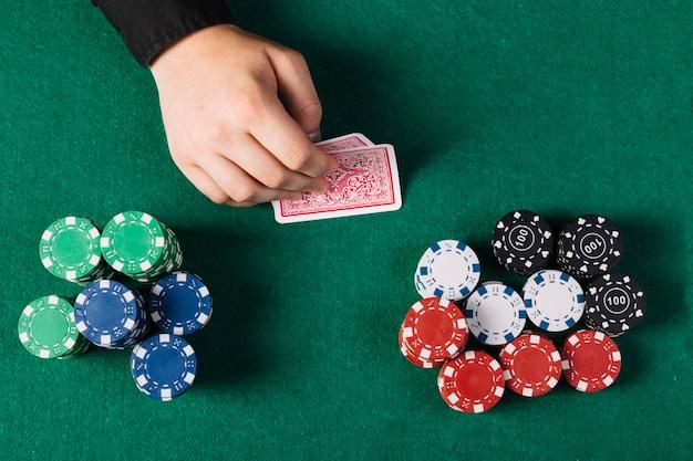 Erhöhte ansicht der hand des spielers mit spielkarten in der nähe von pokertisch Kostenlose Fotos