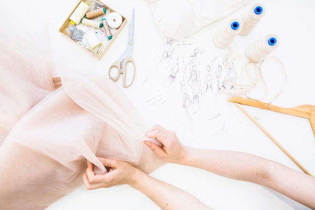 Erhöhte ansicht der hand des weiblichen designers, die gewebe über werktisch hält Kostenlose Fotos