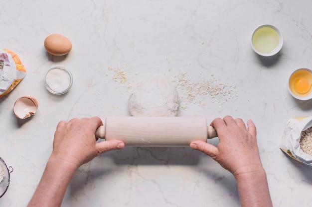 Erhöhte ansicht der hand einer person, die teig mit nudelholz platt macht Kostenlose Fotos