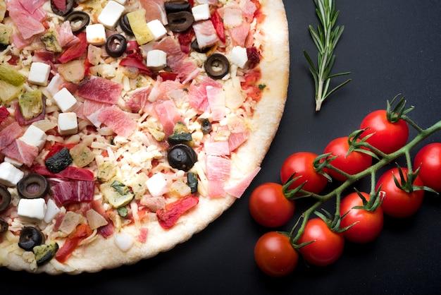 Erhöhte ansicht der italienischen frischen pizza und des bestandteils auf schwarzer oberfläche Kostenlose Fotos