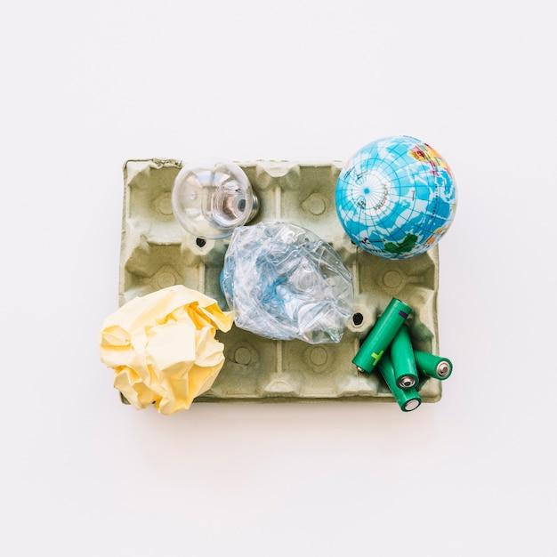 Erhöhte ansicht der kugel, der glühlampe, des zerknitterten papiers, der plastikflasche und der batterien auf eierkarton Kostenlose Fotos
