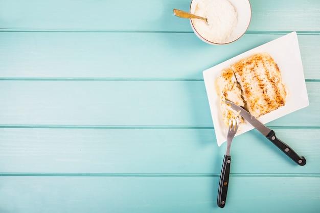 Erhöhte ansicht der lasagne mit gabel und messer Kostenlose Fotos