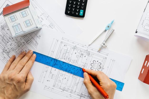 Erhöhte ansicht der menschlichen hand arbeitend an blaupause im immobilienbüro Kostenlose Fotos