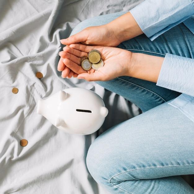 Erhöhte ansicht der menschlichen hand mit münzen nahe piggybank Kostenlose Fotos