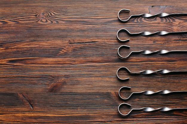 Erhöhte ansicht der metallischen aufsteckspindel vereinbarte in der reihe auf hölzernem hintergrund Kostenlose Fotos