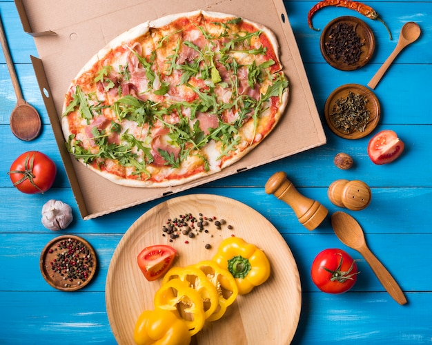 Erhöhte ansicht der pizza; gemüse und gewürze vor einem hölzernen hintergrund Kostenlose Fotos