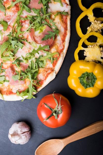 Erhöhte ansicht der pizza mit speck und rucola verlässt nahe geschnittenen gelben grünen pfeffer; knoblauchknolle; tomate und holzlöffel Kostenlose Fotos
