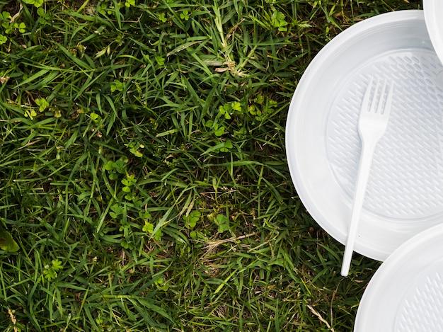 Erhöhte ansicht der plastikplatte und der gabel auf gras am park Kostenlose Fotos