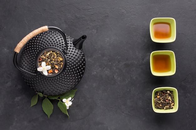 Erhöhte ansicht der strukturierten schwarzen teekanne mit trockenem teebestandteil Kostenlose Fotos