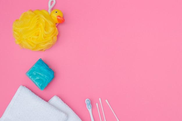 Erhöhte ansicht des badeschwamms; seife; wattestäbchen und handtuch auf rosa hintergrund Kostenlose Fotos