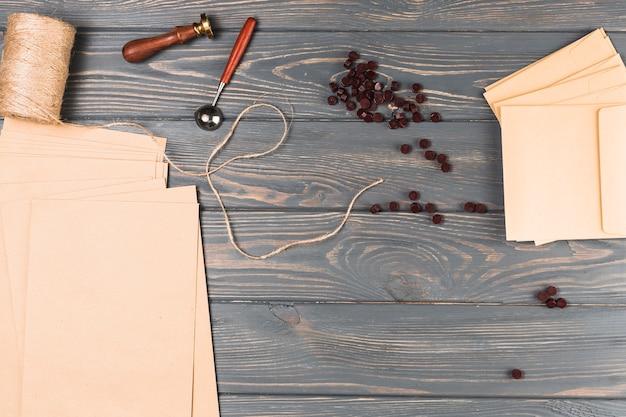 Erhöhte ansicht des braunen wachs; fadenspule; siegelstempel; leere umhüllen karte auf holztisch Kostenlose Fotos