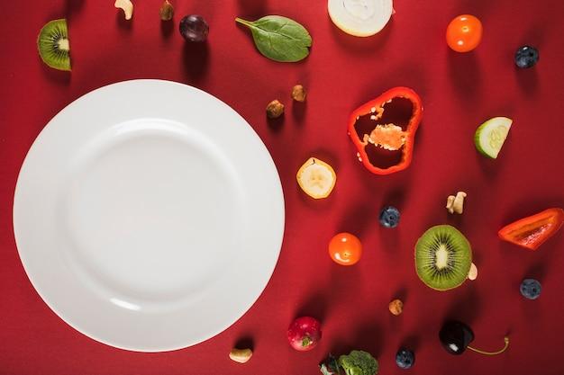 Erhöhte ansicht des frischen rohen lebensmittels mit platte auf rotem hintergrund Kostenlose Fotos