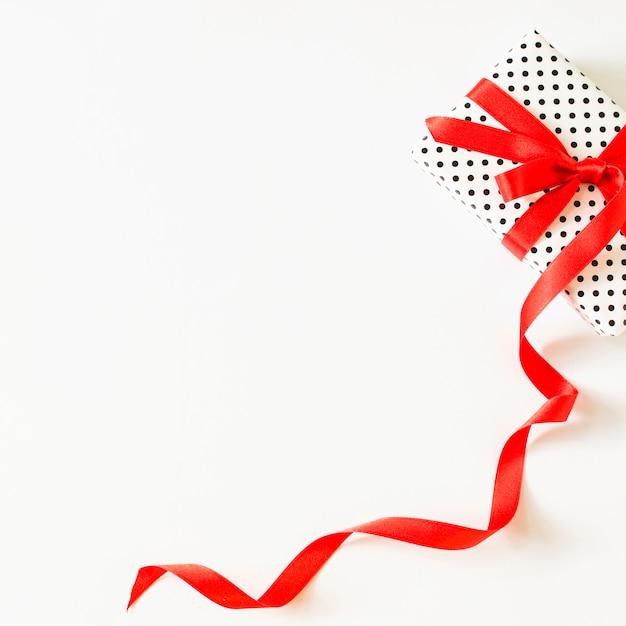 Erhöhte ansicht des geschenks gebunden mit rotem band auf weißer oberfläche Kostenlose Fotos