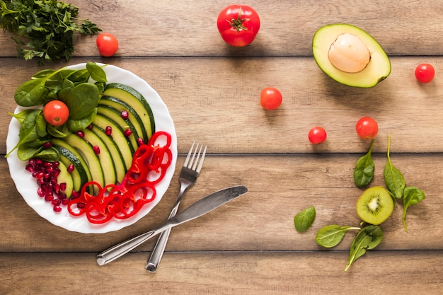 Erhöhte ansicht des gesunden gemüse- und obstsalats in der weißen platte auf holztisch Kostenlose Fotos