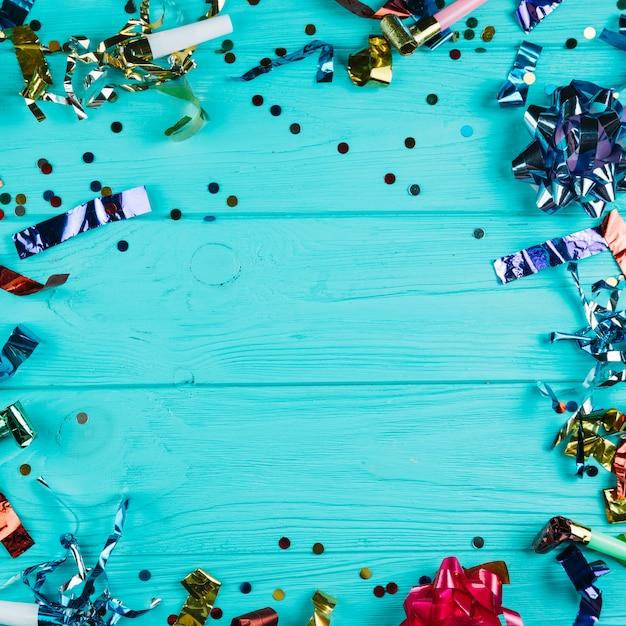 Erhöhte ansicht des glänzenden partydekorationsmaterials über blauem schreibtisch Kostenlose Fotos