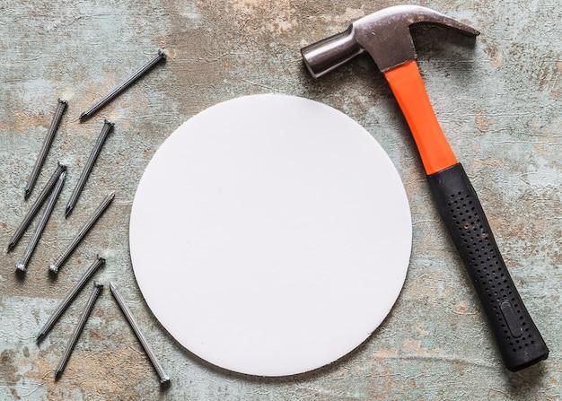 Erhöhte ansicht des hammers, des kreisrahmens und der nägel auf rostigem hintergrund Kostenlose Fotos