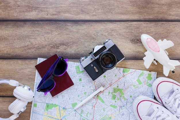 Erhöhte ansicht des kopfhörers; reisepass; sonnenbrille; karte; stift; kamera; schuhe und flugzeug auf hölzernen hintergrund Kostenlose Fotos