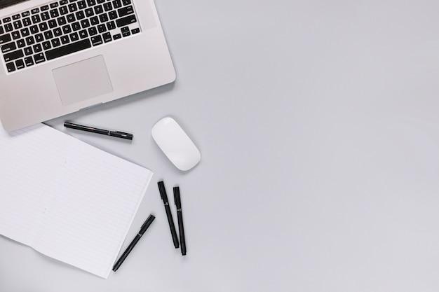 Erhöhte ansicht des laptops; maus; notizbuch und filzstift auf grauem hintergrund Kostenlose Fotos
