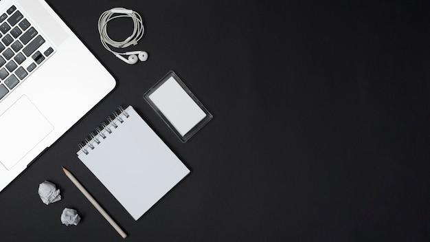 Erhöhte ansicht des laptops; ohrhörer; zerknittertes papier; bleistift; leerer gewundener notizblock und rahmen auf schwarzem hintergrund Kostenlose Fotos