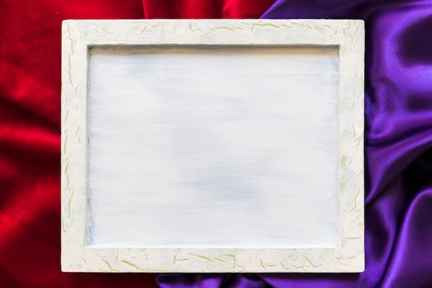 Erhöhte ansicht des leeren bilderrahmens auf rotem und purpurrotem gewebe Kostenlose Fotos
