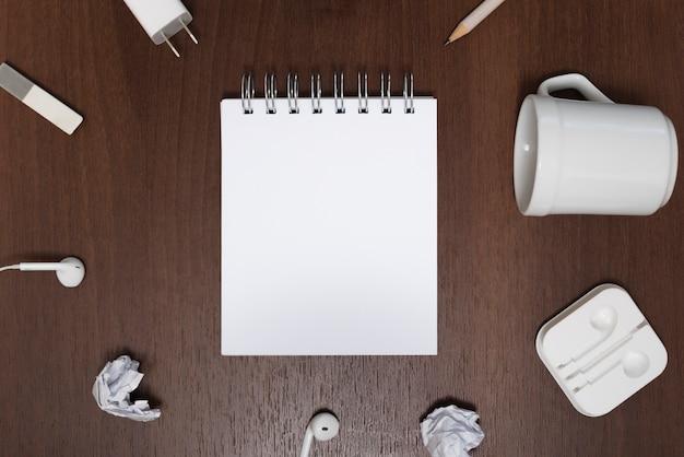 Erhöhte ansicht des leeren notizblocks, umgeben von zerknittertem papier; leere tasse auf hölzernen hintergrund Kostenlose Fotos