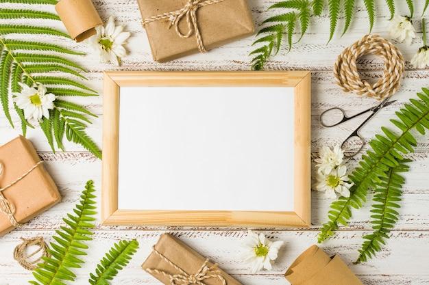 Erhöhte ansicht des leeren rahmens umgeben von geschenken; blätter und weiße blüten Kostenlose Fotos