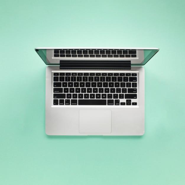 Erhöhte ansicht des offenen laptops auf grünem hintergrund Kostenlose Fotos
