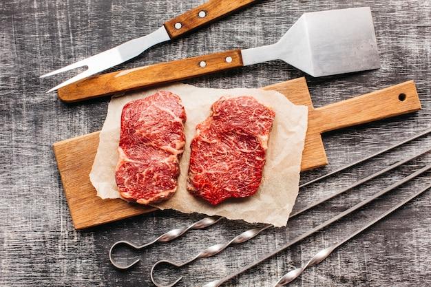 Erhöhte ansicht des rohen steaks und des grillgeräts auf hölzerner strukturierter oberfläche Kostenlose Fotos