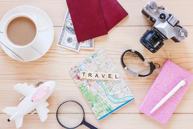 Erhöhte ansicht des verschiedenen reisendenzubehörs mit teeschale auf holzoberfläche Kostenlose Fotos