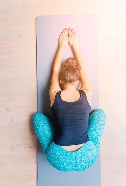 Erhöhte ansicht einer frau, die training auf yogamatte tut Kostenlose Fotos