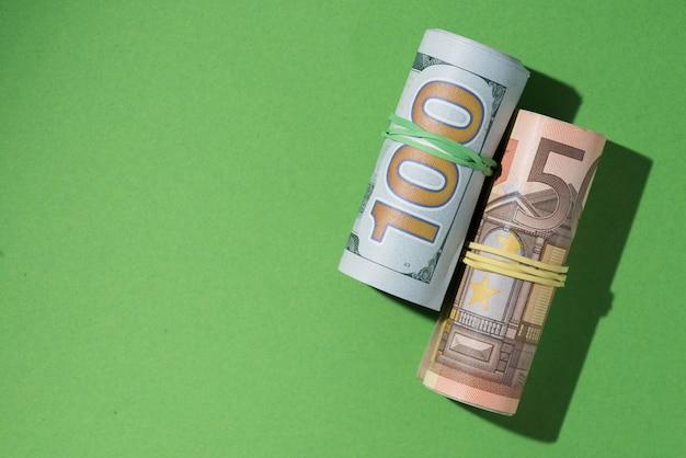 Erhöhte ansicht von aufgerollten banknoten auf grünem hintergrund Kostenlose Fotos