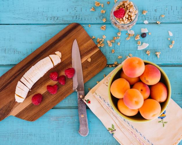 Erhöhte ansicht von bananenscheiben; erdbeeren; pfirsich und hafer auf blauem hölzernem hintergrund Kostenlose Fotos