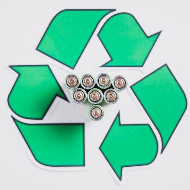 Erhöhte ansicht von batterien im recycling-symbol auf weißem hintergrund Kostenlose Fotos
