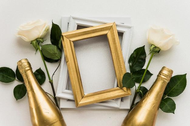 Erhöhte ansicht von bilderrahmen mit zwei rosen und champagnerflasche auf weißer oberfläche Kostenlose Fotos