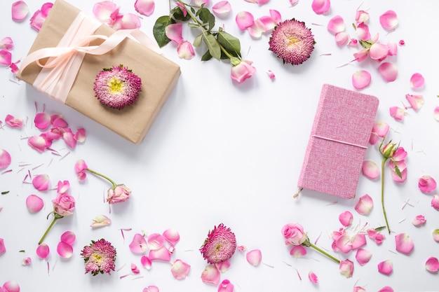 Erhöhte ansicht von blumen; geschenkbox und tagebuch auf weißer oberfläche Kostenlose Fotos