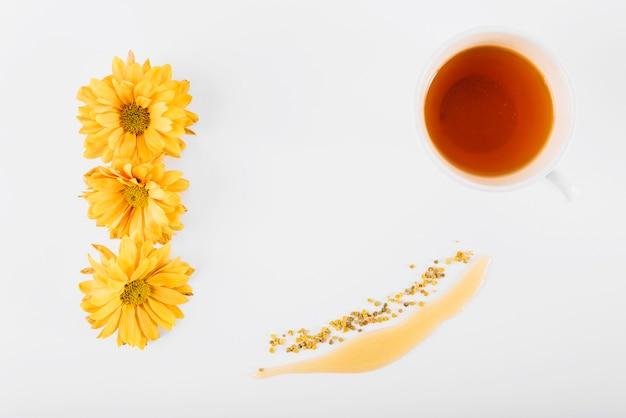 Erhöhte ansicht von blumen; honig; bienenpollen und tee auf weißer oberfläche Kostenlose Fotos