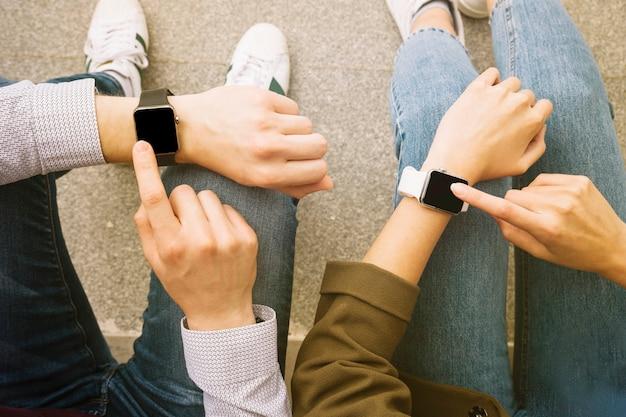 Erhöhte ansicht von den paaren, die zusammen intelligente armbanduhr tragen Kostenlose Fotos