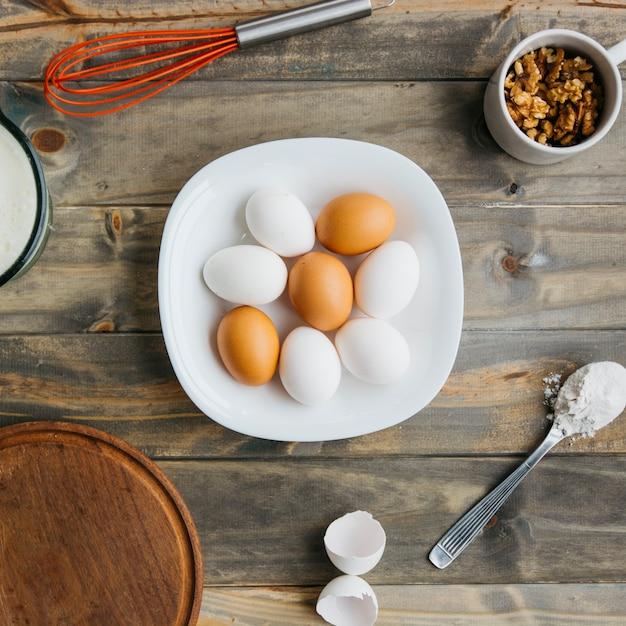 Erhöhte ansicht von eiern; mehl und walnuss mit schneebesen auf hölzernen hintergrund Kostenlose Fotos