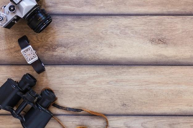 Erhöhte ansicht von ferngläsern; armbanduhr und kamera auf hölzernen hintergrund Kostenlose Fotos