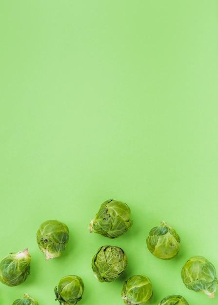 Erhöhte ansicht von frischem rosenkohl auf grüner oberfläche Kostenlose Fotos