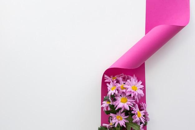 Erhöhte ansicht von gänseblümchenblumen auf rosa verdrehtem band Kostenlose Fotos