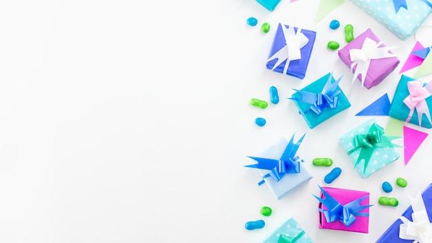 Erhöhte ansicht von geburtstagsgeschenken und -süßigkeiten auf weißer oberfläche Kostenlose Fotos
