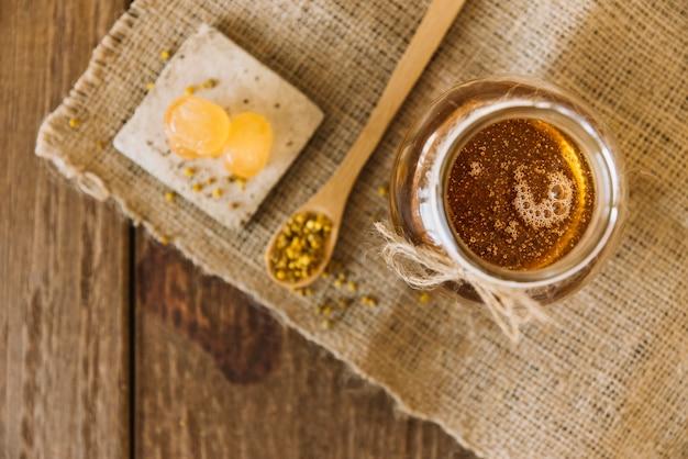 Erhöhte ansicht von honig; bienenblütenstaub und bonbons auf sacktuch Kostenlose Fotos