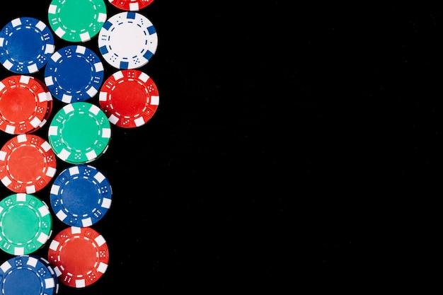 Erhöhte ansicht von pokerchips auf schwarzer oberfläche Kostenlose Fotos